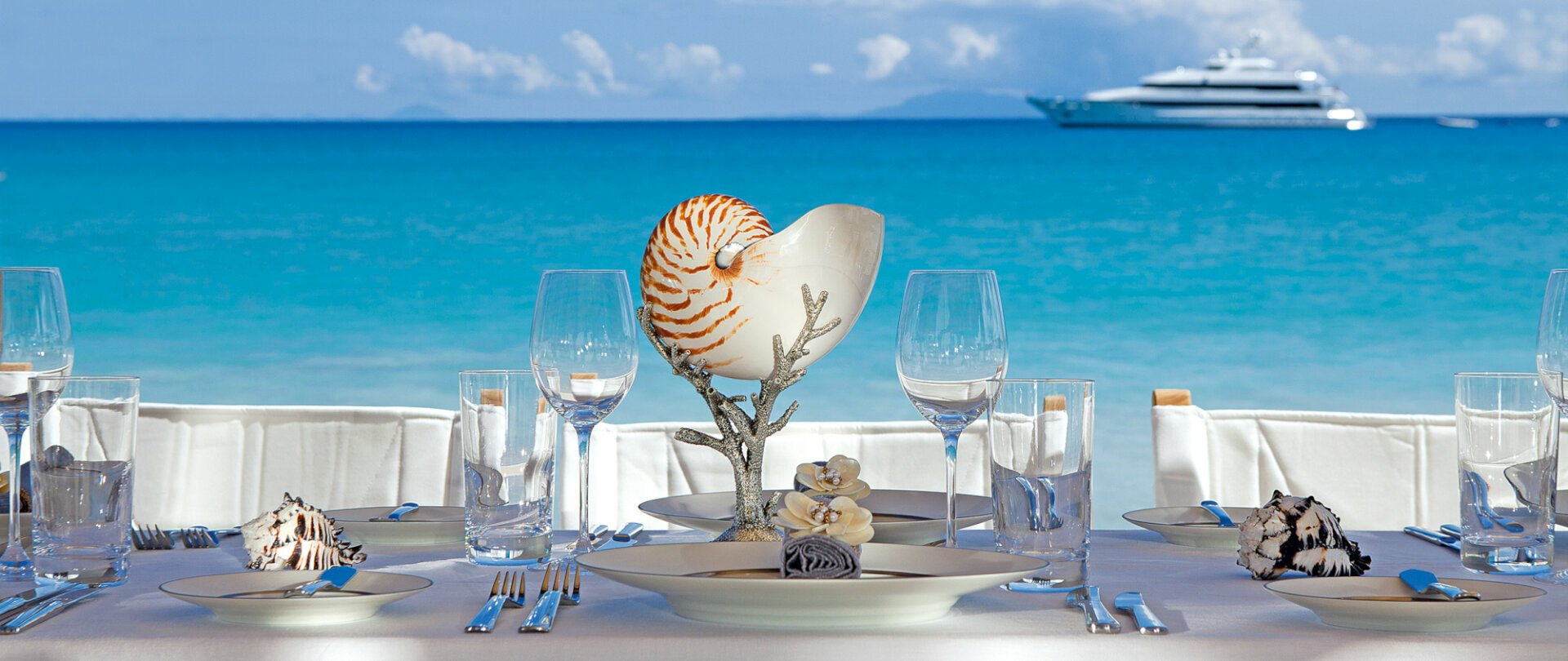 Dining on the beach with view of the charter yacht