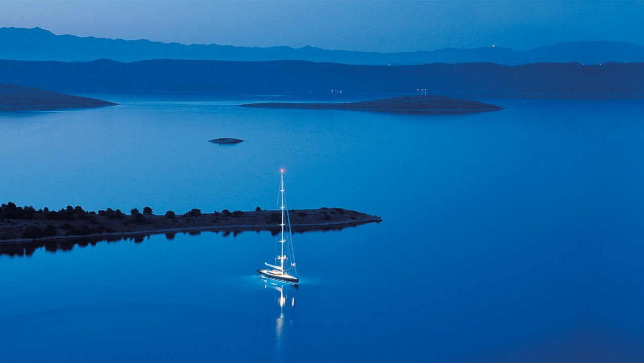 Sailing yacht anchored by some islands in Croatia at dusk