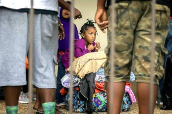A child sitting on the floor with her clothes, after hurricane Irma