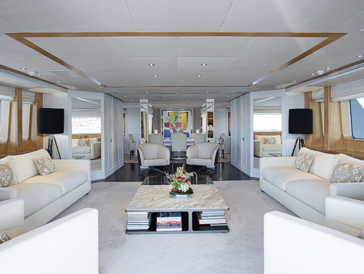 Deep Blue II The interior living space of the Deep Blue II yacht, with white table, sofas, walls, floor and ceiling