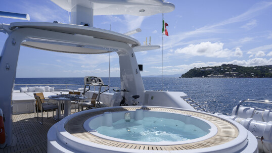 A white jacuzzi on the upper deck of the Deep Blue II yacht, beside deck chairs