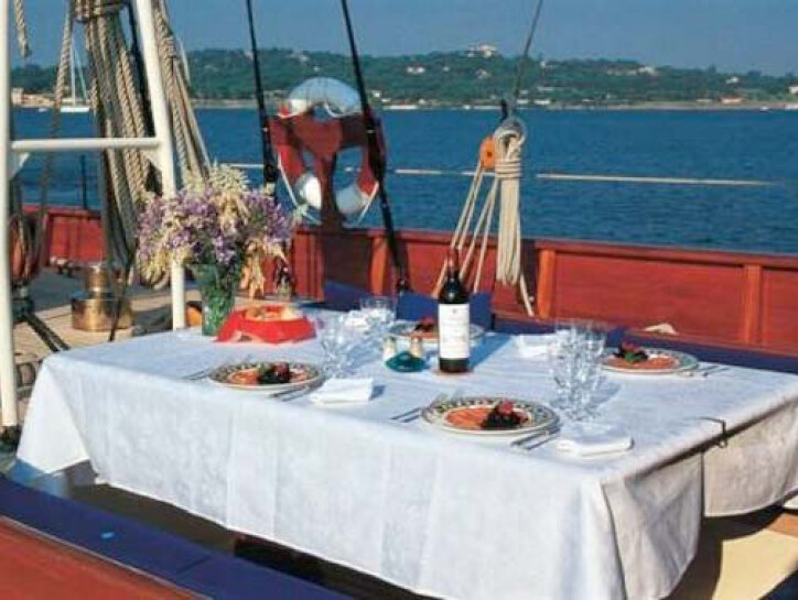 Thendara A dining table on the upper deck of the Thendara, with gourmet food laid out and a bottle of red wine