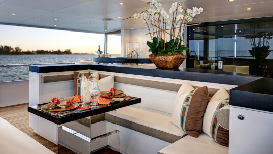 Living room space on Highlander yacht, with crocodile skin seats and wooden interior