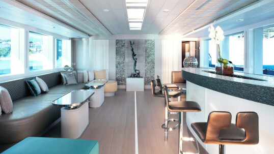 The outer deck of the Philmi Yacht, with wooden table and chairs around it