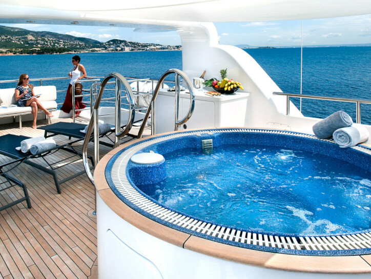 Christina G A jacuzzi sitting on the upper deck of the Christina G yacht, beside sunbathing beds