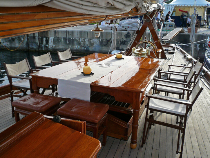 Moonbeam IV Dining area on the upper deck of the Moonbeam IV, consisting of a wooden table and seats with leather cushions on them